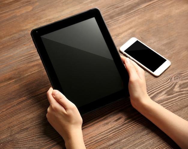 Telefon komórkowy i kobiece dłonie za pomocą tabletu