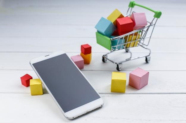 Telefon komórkowy i koszyk, zakupy online, koncepcja zakupów na telefon komórkowy