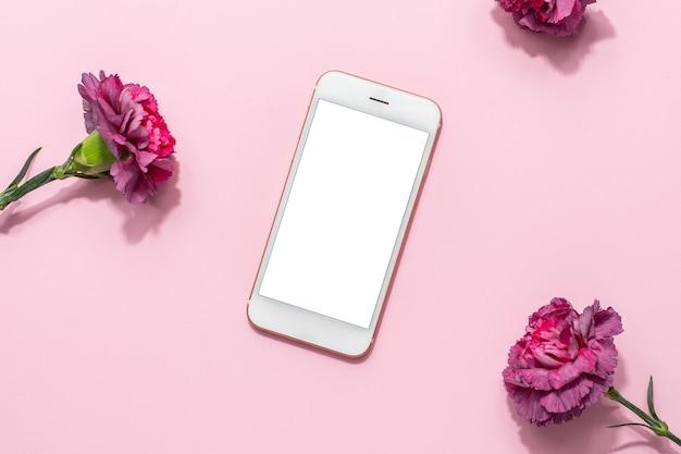 Telefon komórkowy i różowe kwiaty na różowym pastelowym stole