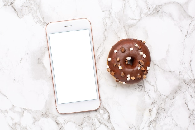 Telefon komórkowy i słodki pączek na marmurowym tle
