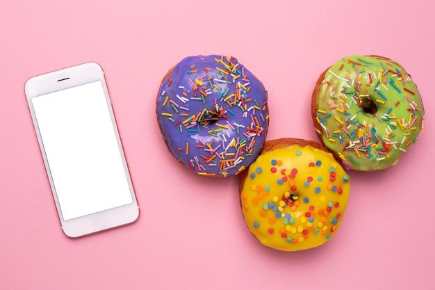 Telefon komórkowy i słodkie pączki na różowym tle płaski leżał