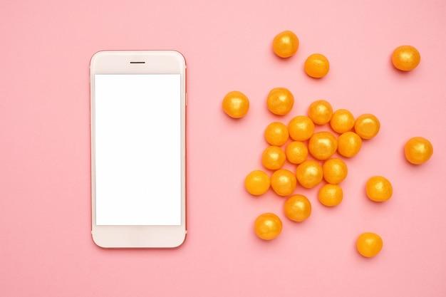 Telefon komórkowy i słodkie żółte cukierki na różowej technologii