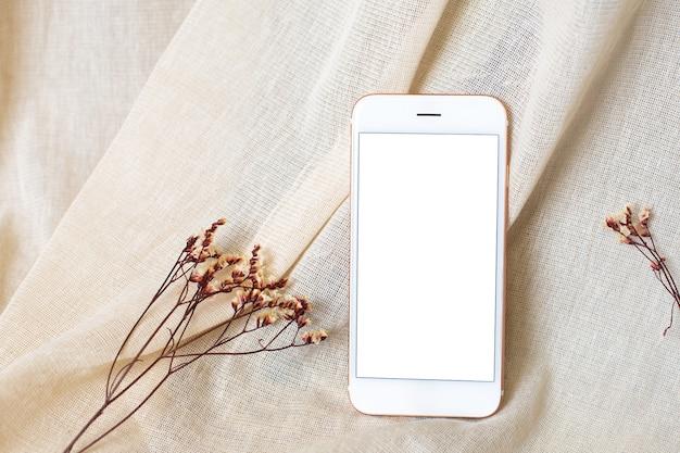 Telefon komórkowy i suszone kwiaty na beżowej naturalnej bawełnianej tkaninie.