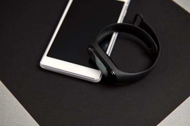 Telefon komórkowy i zegarek cyfrowy lub czarny fitness tracker na czarnej kartce papieru na szarym tle. martwa natura w czerni i bieli. leżał na płasko
