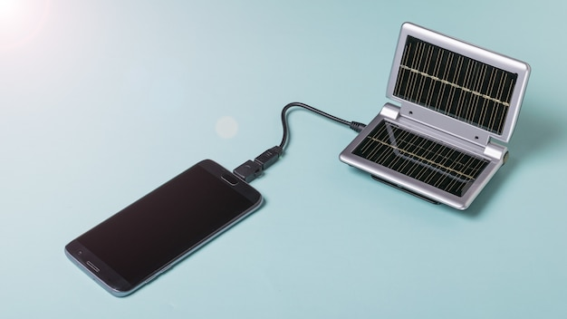 Telefon komórkowy jest ładowany za pomocą przenośnej ładowarki zasilanej energią słoneczną. wykorzystanie energii słonecznej. technologia przyszłości.