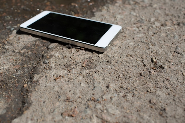 Telefon komórkowy leżący na asfalcie chodnika