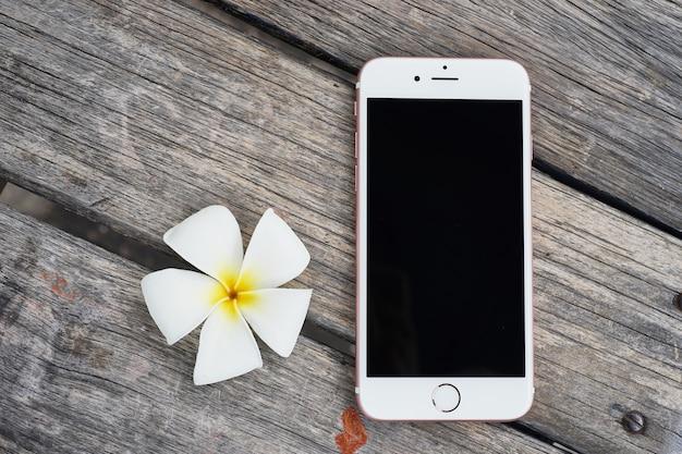 Telefon komórkowy lub przyrząd z pięknym kwiatem na drewnianym tle