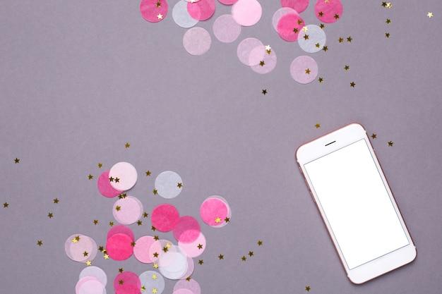 Telefon komórkowy makieta i różowe konfetti ze złotymi gwiazdkami na szaro