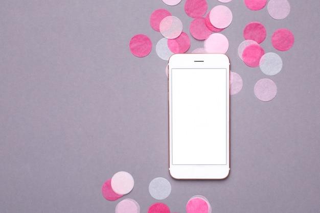 Telefon komórkowy makieta z różowym konfetti na szaro