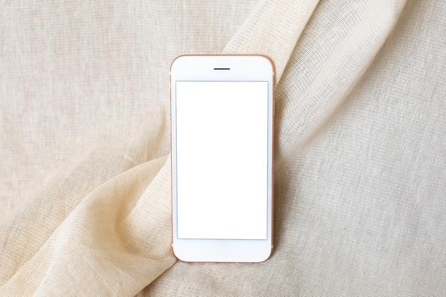 Telefon komórkowy na beżowej, naturalnej tkaninie bawełnianej.
