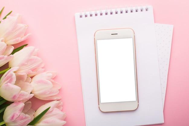 Telefon komórkowy, notatnik i wiosenne różowe tulipany. leżał płasko