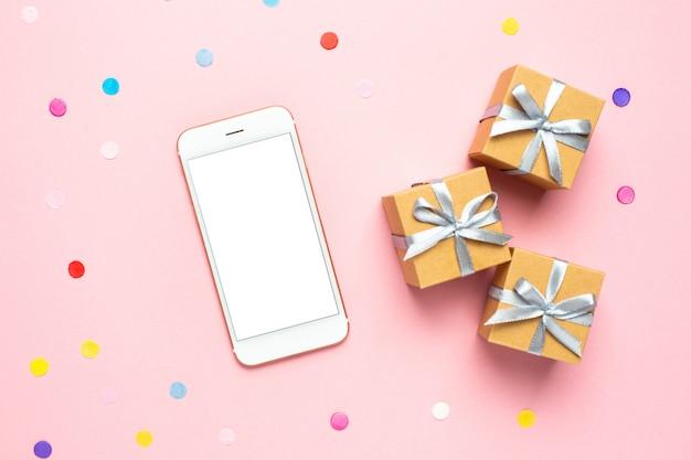Telefon komórkowy, obecne pudełka i kolorowe konfetti na różowym stole.