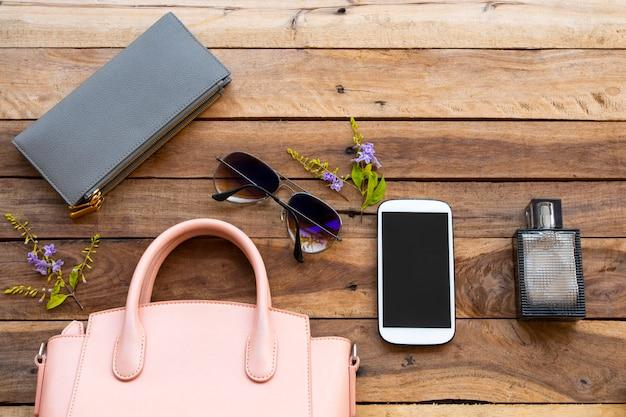 Telefon komórkowy, okulary przeciwsłoneczne, torebka, perfumy i różowa torebka kolekcja kobiety lifestyle'owej
