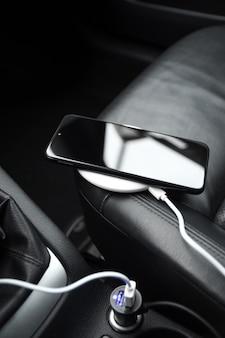 Telefon komórkowy, smartfon ładuje akumulator, bezprzewodowe ładowanie we wtyczce samochodowej z bliska
