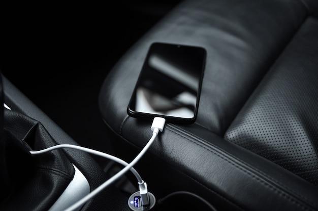Telefon komórkowy, smartfon ładuje akumulator, ładowanie z bliska wtyczki samochodowej