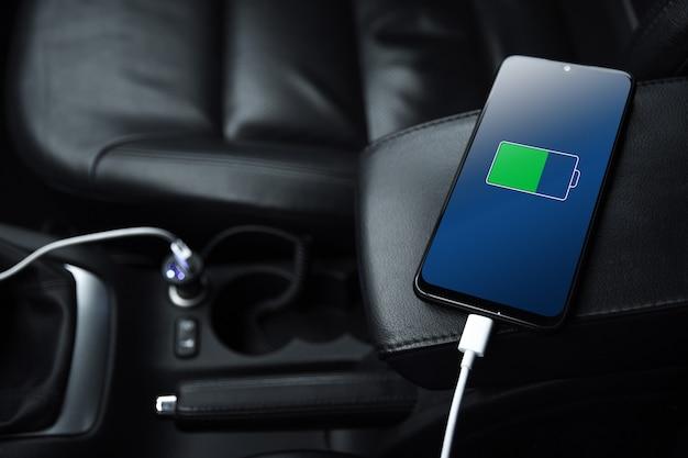 Telefon komórkowy, smartfon, telefon komórkowy jest naładowany, ładowanie baterii za pomocą ładowarki usb w samochodzie. nowoczesne czarne wnętrze samochodu.
