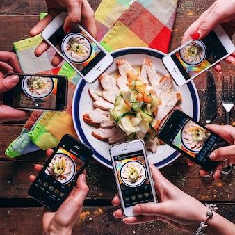 Telefon komórkowy w rękach ludzie robią zdjęcia smacznego jedzenia
