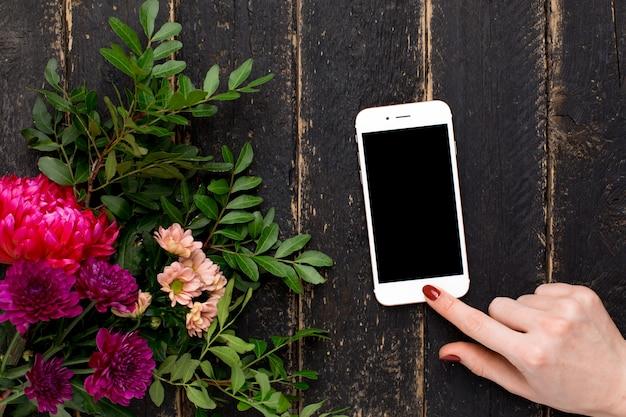 Telefon komórkowy w żeńskiej ręce i bukiecie kwiaty na czarnym drewnie