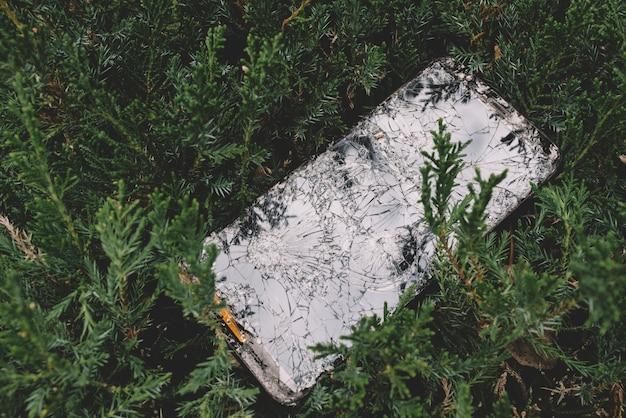 Telefon komórkowy widziany z góry rozbił się w krzakach roślin