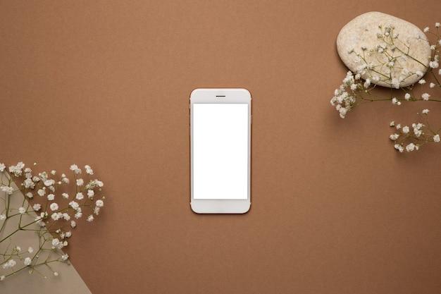 Telefon komórkowy z białym ekranem i suchą gałązką kwiatową oraz jasnobrązowym kamieniem.