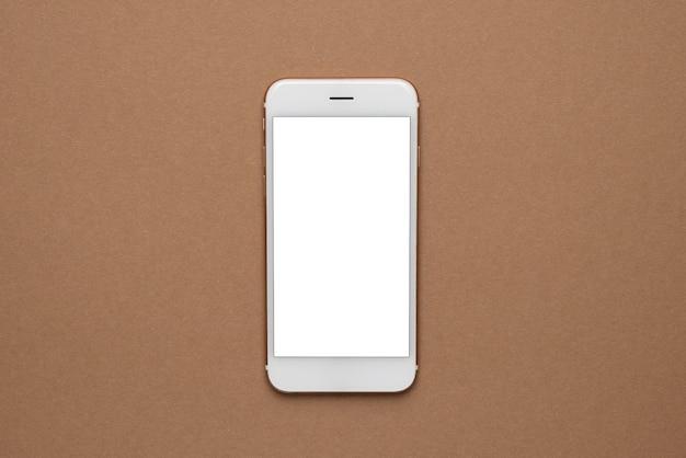 Telefon komórkowy z białym ekranem na jasnobrązowym tle. trend, minimalna koncepcja z widokiem z góry copyspace
