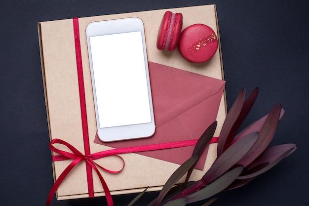 Telefon komórkowy z kwiatem i prezentem w ciemności