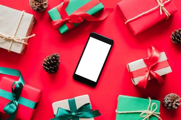Telefon komórkowy z pudełkiem na prezentprezentuje na czerwonym tle na boże narodzenie i koncepcję szczęśliwego nowego roku.