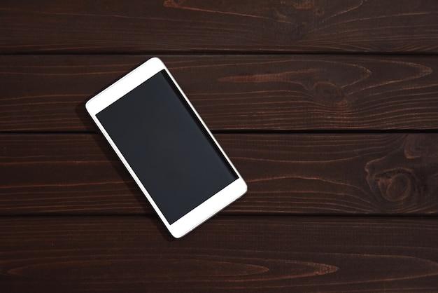 Telefon komórkowy z pustym ekranem na drewnianym stole