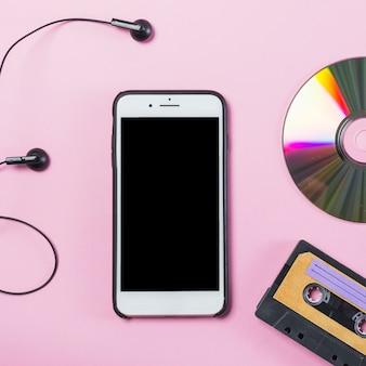 Telefon komórkowy z słuchawką; dysk i kaseta na różowym tle
