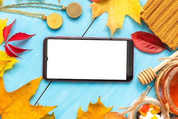 Telefon na stole z poranną kawą i miodem. jesienią.