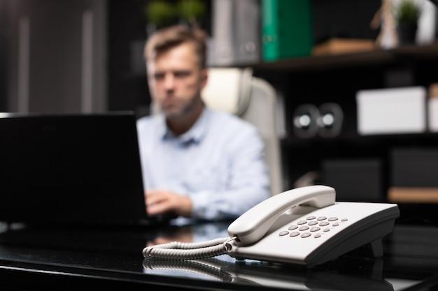 Telefon stacjonarny z bliska młodego człowieka siedzącego przy biurku komputerowym.