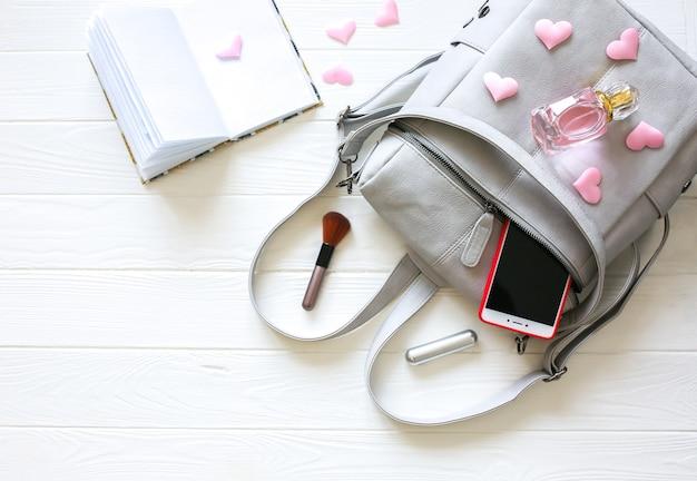 Telefon, stylowa torba i perfumy na białym tle. piękne mieszkanie leżało. rzeczy dla kobiety biznesu. notuj harmonogram książki. zestaw do makijażu. prezent dla dziewczynki z sercami.