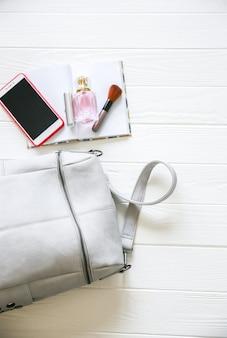 Telefon, stylowa torba i perfumy na białym tle. piękne mieszkanie leżało. rzeczy dla kobiety biznesu. notuj harmonogram książki. zestaw do makijażu.