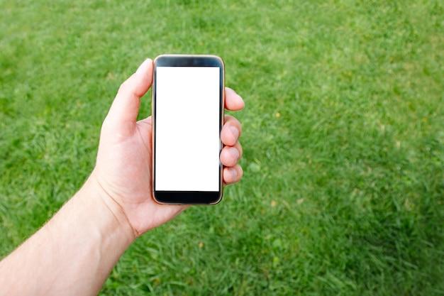 Telefon w ręku mężczyzn w tle bujnej zielonej trawie. makieta do projektowania