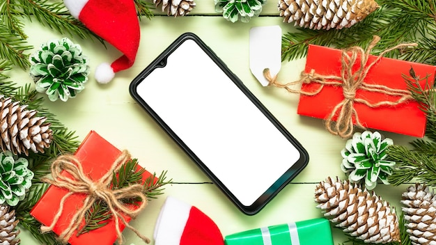 Telefon w świątecznej kompozycji z szyszkami i prezentami.