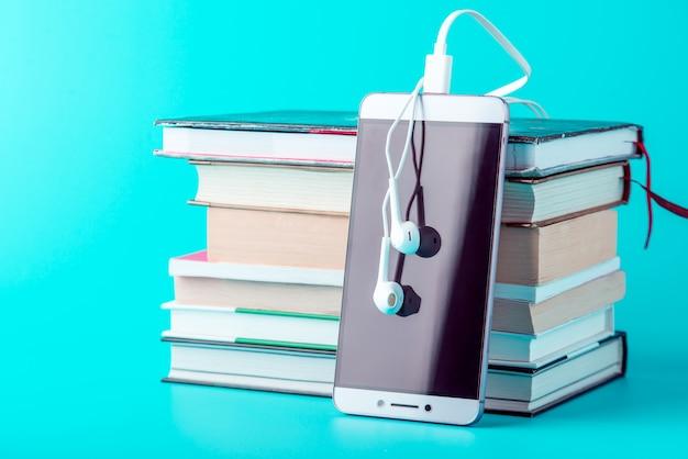 Telefon z białymi słuchawkami obok stosu książek na niebieskim tle.