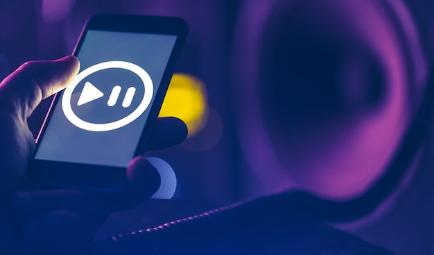 Telefon z ikoną słuchania muzyki na ekranie na ciemnym tle, miejsce.