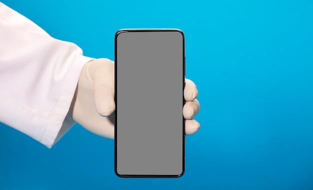 Telefon z makietą szarego ekranu w rękach lekarza w rękawiczkach sanitarnych