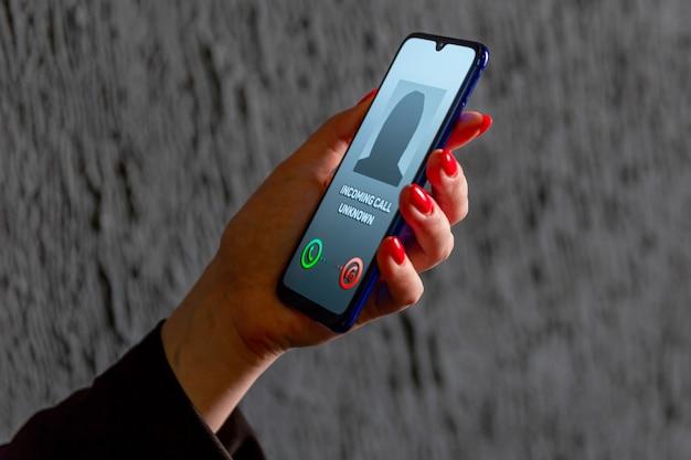 Telefon z nieznanego numeru. oszustwo, oszustwo lub phishing z koncepcją smartfona. żartobliwy rozmówca, oszust lub nieznajomy. kobieta odbiera połączenie przychodzące. osoba oszukańcza z fałszywą tożsamością.