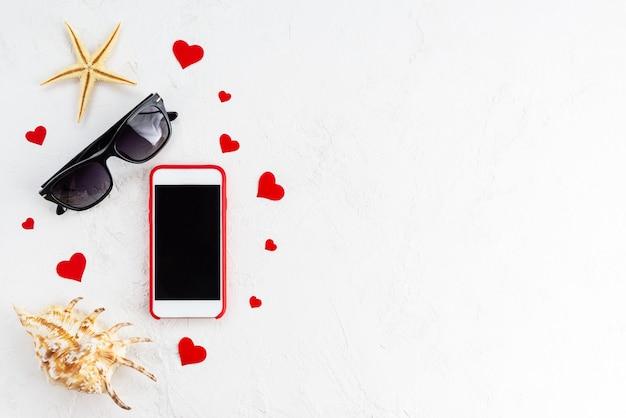 Telefon z okularami przeciwsłonecznymi, rozgwiazdą, muszlą i sercami na białej powierzchni