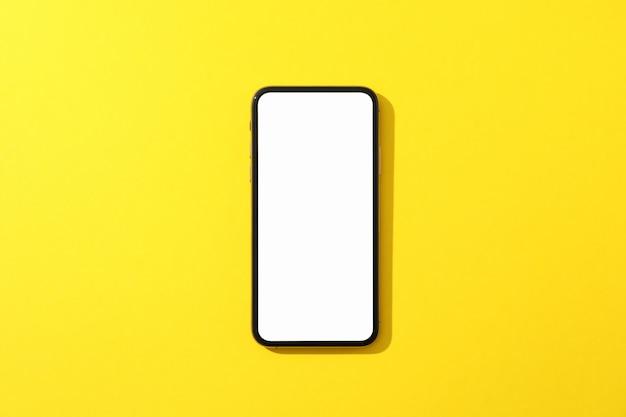 Telefon z pustym ekranem na żółtej powierzchni