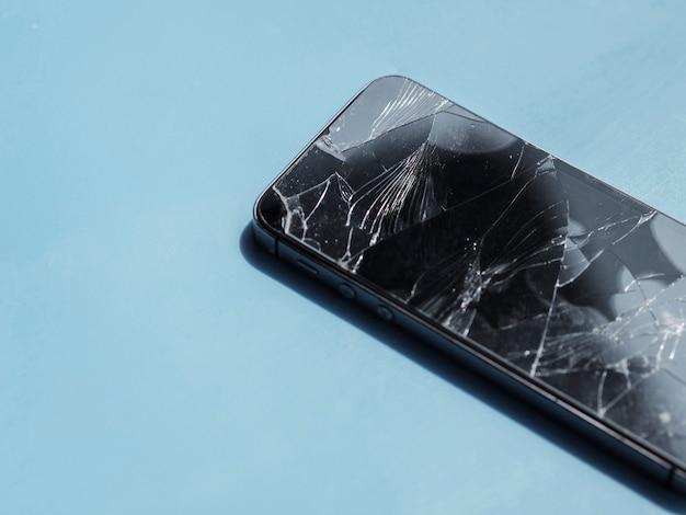 Telefon z rozbitym ekranem na niebieskim tle