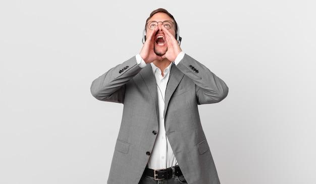 Telemarketer biznesmen czuje się szczęśliwy, wydając wielki okrzyk z rękami przy ustach