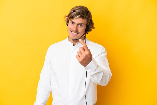 Telemarketer człowiek pracujący z zestawem słuchawkowym na białym tle na żółtej ścianie robi nadchodzący gest