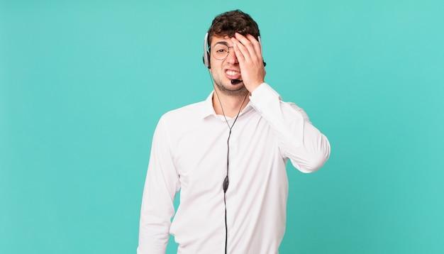 Telemarketer czuje się znudzony, sfrustrowany i senny po męczącym, nudnym i żmudnym zadaniu, trzymając twarz dłonią