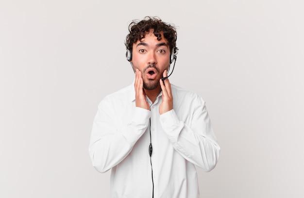 Telemarketer czuje się zszokowany i przestraszony, wygląda na przerażonego z otwartymi ustami i dłońmi na policzkach