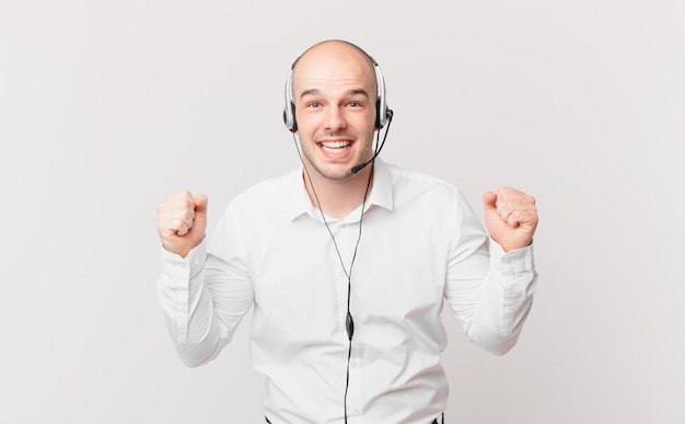Telemarketer czuje się zszokowany, podekscytowany i szczęśliwy, śmieje się i świętuje sukces, mówiąc wow!