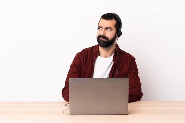 Telemarketer kaukaski mężczyzna pracujący z zestawem słuchawkowym i laptopa, mając wątpliwości, patrząc w bok