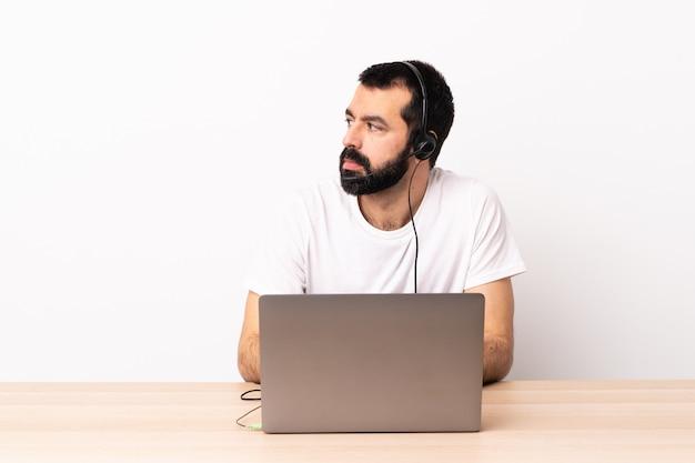 Telemarketer kaukaski mężczyzna pracujący z zestawem słuchawkowym i laptopa patrząc z boku