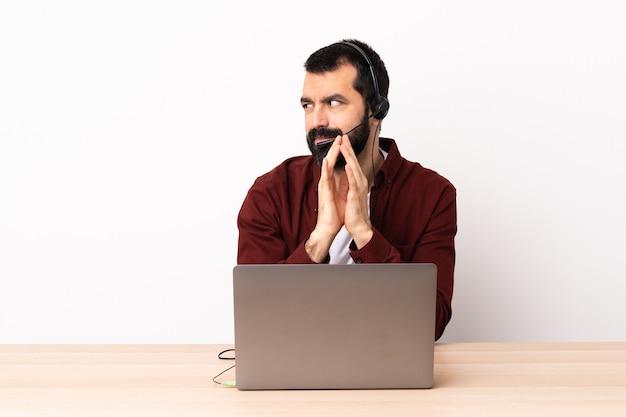 Telemarketer kaukaski mężczyzna pracujący z zestawem słuchawkowym i laptopem coś knuje